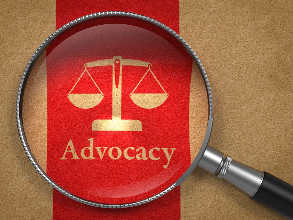 Advocacy Concept Magnifying Glass with Word Advocacy and Icon of Scales in Balance on Old Paper with Red Vertical Line Background.-1